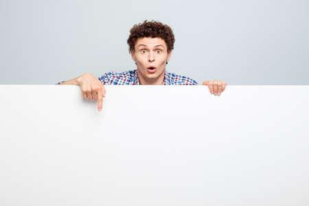 Vrolijke jonge man die achter de witte lege banner staat en naar beneden wijst op een witte copyspace geïsoleerd op een lichtgrijze achtergrond