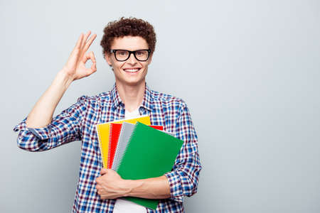 Young handsome student man with curly hair in glasses and in checkered shirt, showing ok sign isolated on light gray background with copy space for text
