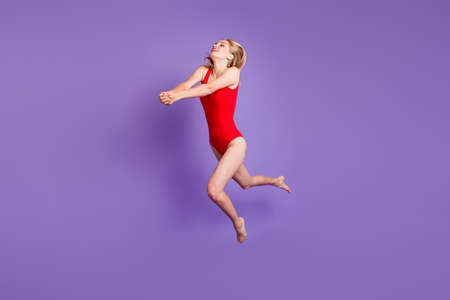 Concept of a beach holiday. Full-size portrait of young blonde girl jumped up to fight off a pitch of a volleyball isolated on violet background