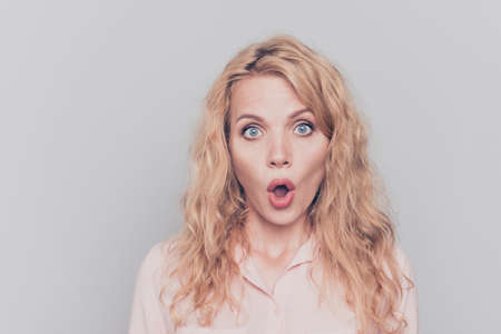 Portrait of attractive cute nice curly-haired blonde gorgeous caucasian young girl being surprised. Copy space. Isolated over grey background