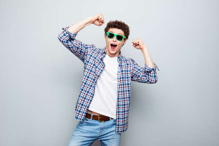 Portrait of happy brunet man with curly hair wearing in casual clothes and summer glasses, celebrate begining of holiday isolated on light gray background