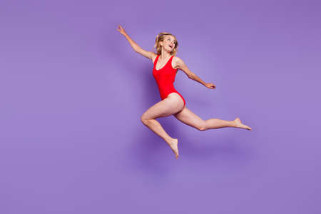 Concept of carefree summer. Full-body portrait of beautiful young female model with blond hair flying isolated on purple background