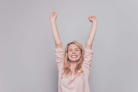 Wondered blond hair woman celebrates victory by raising her hands up isolated on gray background