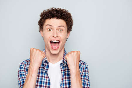 We make it! Close up portrait of stylish happy young guy with hands clasped in fists and loud yell in happiness isolated on light gray background with copy space for text