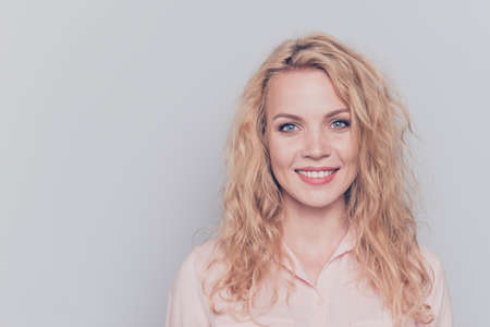 Portrait of young attractive nice cute caucasian smiling curly-haired blonde girl wearing casual shirt. Isolated over grey background Stock Photo