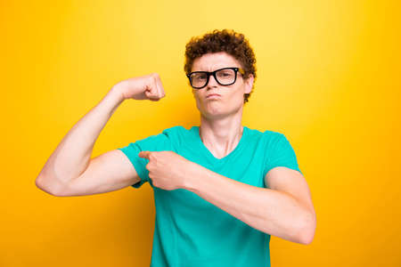 Handsome curly-haired young guy wearing casual green t-shirt and glasses, showing muscles. Isolated over yellow background Banque d'images - 106309020