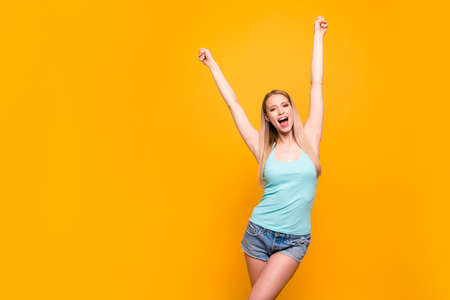 Charming young model with long blond hair raises her fists up and triumphantly screams goal isolated on shine yellow background with copy space for text