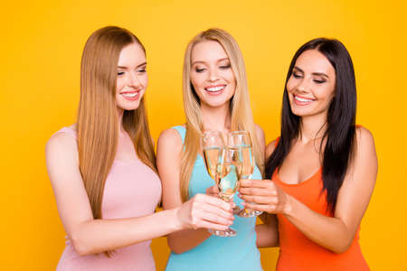 Portrait of cheerful positive girls holding alcohol beverage in hands clicking glasses, blonde brunette ginger enjoying free time together having beaming smiles isolated on bright yellow background