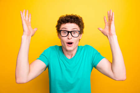 Handsome curly-haired shocked young guy wearing casual green t-shirt and glasses, showing surprised gesture. Isolated over yellow background