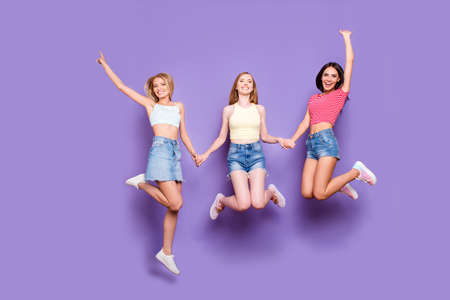 Portrait of foolish playful girls holding hands jumping in air enjoying vacation celebrating achievement isolated on vivid violet background