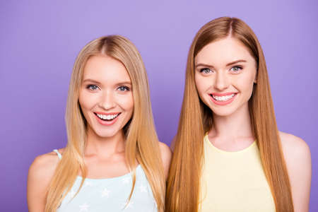 Head shot portrait of cheerful positive girls with white healthy smile having long hair looking at camera isolated on violet background. Dental dentist stomatology concept Stock Photo
