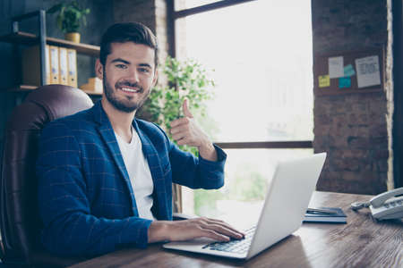 Portrait of attractive handsome young brunet smiling executive worker man, sitting in office workstation workplace, using laptop, showing thumb up