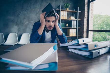 Very tired assistant hid his head with a diary and waits for the end of the working day Stock Photo