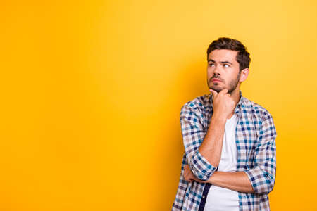 Close up portrait of thoughtful man who looks away touching his chin and weighs the pluses and minuses of the offer isolated on bright yellow background with copy space for text Stock Photo