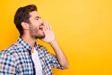 Close up portrait of  �heerful young brunet man in checkered shirt  is holding hand near her open mouth isolated on vivid yellow background with copy space for text Foto de archivo