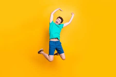 Full size length body picture of handsome curly-haired playful young guy wearing casual green t-shirt, shorts, shoes, jumping, hands up, celebrating prize winning. Isolated over yellow background Standard-Bild