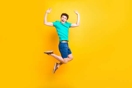 Full size length body picture of handsome curly-haired playful young guy wearing casual green t-shirt, shorts, shoes, jumping in air, raising hands up. Isolated over yellow background Stock Photo