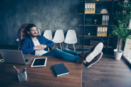 Attractive handsome young brunet bearded executive worker smiling man in office workstation workplace, sitting in chair, legs lying on table, dreaming, having rest, break