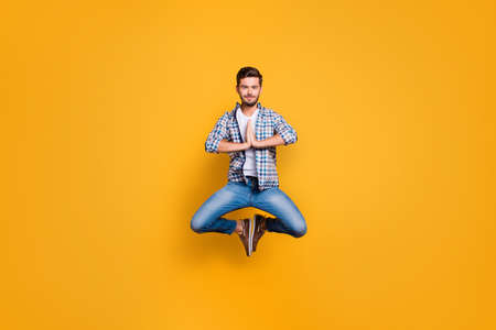 Full-body portrait of levitates in the air meditating and concentrating isolated on shine yellow background Фото со стока