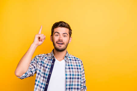 Portrait of handsome man with a beard raised his finger up since he knows the solution to the problem isolated on vivid yellow background with copy space for text