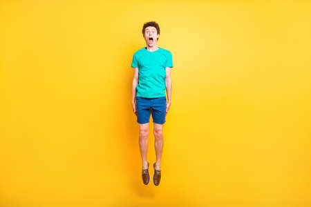 Full size length body picture of handsome curly-haired playful young guy wearing casual green t-shirt, shorts, shoes, jumping up in air, opened mouth. Isolated over yellow background Stock Photo