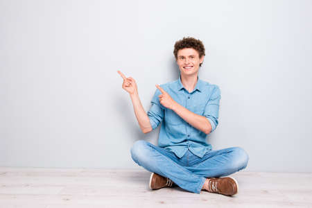 Handsome wavy curly-haired cheerful young guy wearing casual jeans denim, shoes, sitting on floor with crossed legs, pointing showing with two fingers. Copy space. Isolated over light grey background Stock Photo