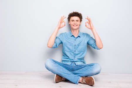 Handsome curly-haired cheerful smiling young guy wearing casual jeans denim, shoes, sitting on floor, showing double ok sign. Copy space. Isolated over light grey background