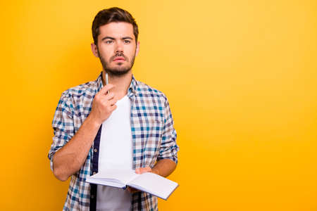 Portrait of thoughtful, serious, bearded man holding copybook isolated on shine yellow background with copy space for text