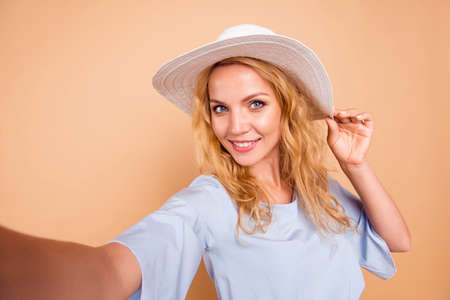 Portrait of young lovely attractive caucasian curly-haired charming gorgeous smiling woman wearing sunhat taking self photo. Isolated over pastel yellow background