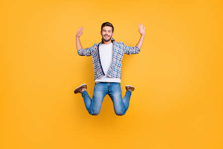 Full-legh portrait of happy guy in casual outfit jumping with hands up isolated on vivid yellow background Фото со стока
