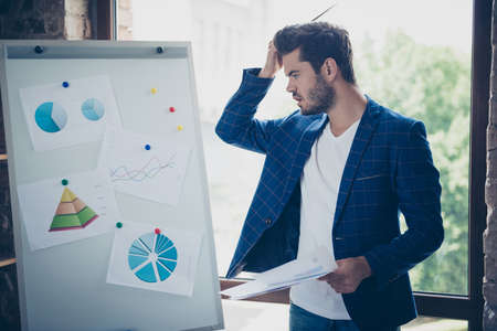 Attractive handsome young brunet bearded executive worker confused man, financer, analytic at workstation workplace. Making graphic presentation on white board
