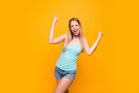 Happy blond girl raises her hands in fist isolated on vivid yellow background with copy space for text Stock Photo