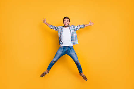 Full-legh portrait of of crazy and excited handsome man jumping up like a star isolated on shine yellow background Stok Fotoğraf