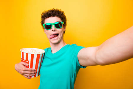 Self portrait of handsome curly-haired childish young guy with popcorn box, wearing casual green t-shirt and colorful sun glasses, showing tongue out. Isolated over yellow background