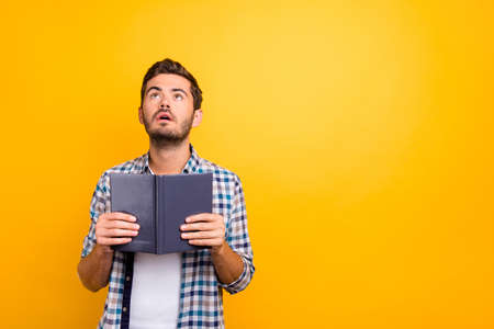 Portrait of thoughtful man holding book looking up isolated on shine yellow background with copy space for text