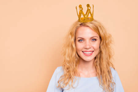 Portrait of attractive beautiful curly-haired cheerful blonde caucasian young girl wearing golden crown on head. Copy space. Isolated over grey background