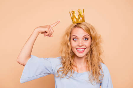 Portrait of young attractive charming nice cute caucasian curly-haired blonde girl wearing golden crown and blue dress, pointing to diadem, toothy smile. Isolated over beige background Stock Photo