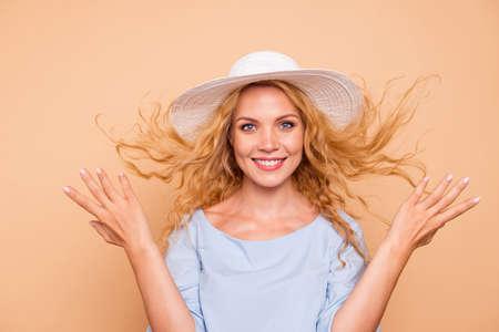 Retrato de joven hermosa atractiva caucásica rizada encantadora hermosa sonriente mujer vistiendo sombrero para el sol, viento que sopla el pelo. Aislado sobre fondo amarillo pastel