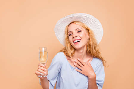Portrait of attractive beautiful curly-haired cheerful blonde caucasian young girl wearing blue dress and sunhat drinking glass of champagne. Isolated over grey background
