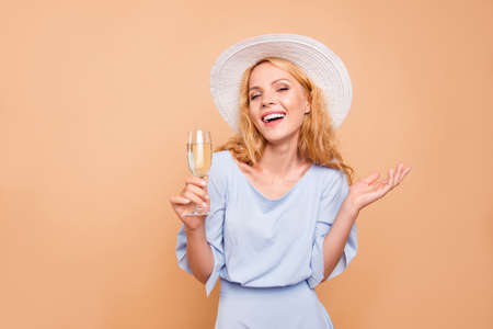Portrait of attractive beautiful curly-haired cheerful blonde caucasian young girl wearing blue dress and sunhat holding glass of champagne. Isolated over grey background