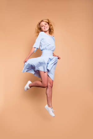 Vertical full body size length view photo portrait of attractive pretty stunning fit slim woman jumping up holding dress isolated on pastel bright vivid color background