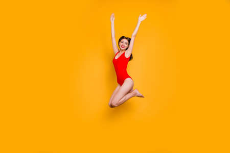 Freedom restless concept. Full-size portrait of excited girl with rise up hands jumping up isolated on yellow background
