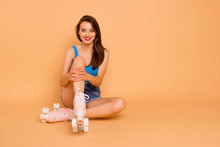 Full-size portrait of creehful and cute sweet girl sits on the floor in roller skates and hugging her knees looking at camera isolated on pastel peach background with copy space for text Foto de archivo - 106299820