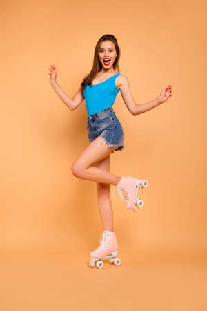 Full-body vertical portrait of stylish coquette girl happy celebrate beginning of the roller-skating season by raising her hands up and smiling broadly isolated on pastel peach background