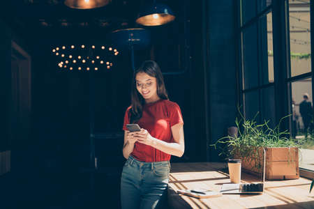 Young charming girl stands with cafe with smartphone in hands and smiles sending a message Фото со стока