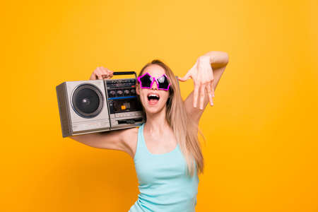 Attractive nice cute straight-haired beautiful blonde caucasian smiling girl, wearing casual shirt, sun glasses star shape. Holding boom box, enjoying music. Isolated over yellow background