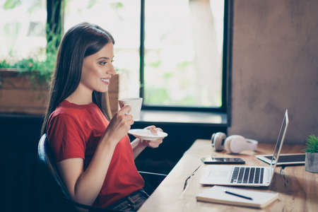 Little bit of time for myself! Side profile view photo of cute beautiful woman drinking coffee and watching a webinar on her netbook, sitting at the table 스톡 콘텐츠