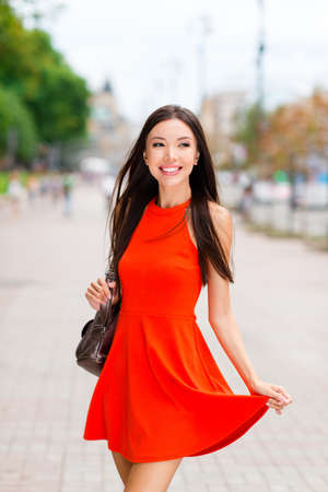 Vertical portrait of beautiful and young Asian woman with leather backpack hold on to the hem of the dress and looks aside against a blurred background of cityscape Stock Photo
