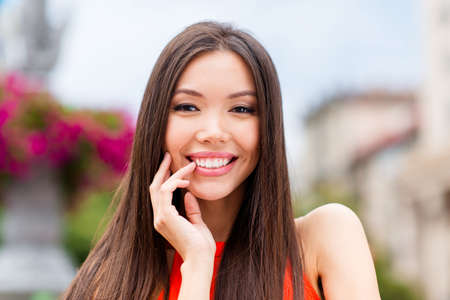 Close up portrait of of beautiful, dreamy young woman with brunette hair and lovely smile looking at camera touching the lips by finger blurred background