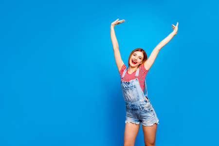 Portrait of nice vivid girlish red straight-haired happy young girl with opened mouth, stretching smiling having fun, isolated over blue background, copy space Imagens